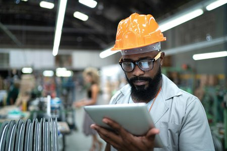 Engineer with tablet in factory